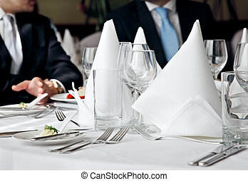 business lunch meeting - two business people no faces over a...
