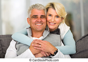 middle aged couple relaxing at home - happy loving middle...