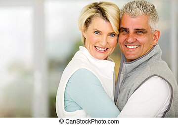 middle aged couple embracing - beautiful middle aged couple...