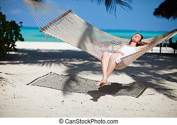 Tropical vacation - Beautiful woman relaxing in hammock on...