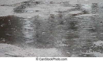 Rain dripping through the puddles. Raindrops. - Heavy rain...