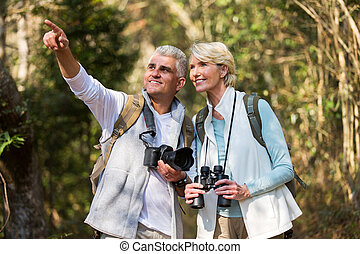 middle aged couple hiking outdoors in forest - active middle...