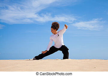 Thai-chi in the dunes - Young attractive woman making...
