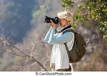 senior hiker taking photos with digital camera - happy...