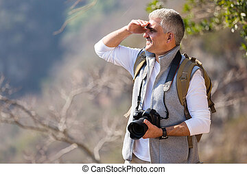 mature man hiking in mountain with dslr camera