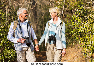 mature couple hiking in mountain - happy mature couple...