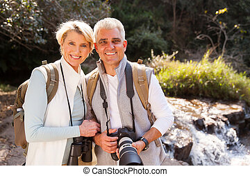 mid age couple standing in mountain valley - portrait of...