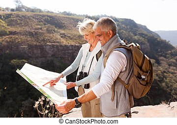 middle aged hikers looking at a map - active middle aged...