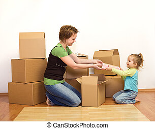 Woman and little girl in a new home unpacking from cardboard...