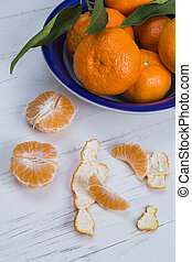 Clementines in a blue bowl with peeled segments and pieces...