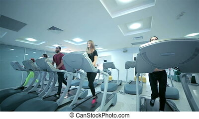 Group sessions on the treadmill. Sports people running on...