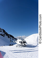 White rescue helicopter parked in the mountains - White...