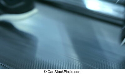 Treadmill closeup. Feet running on.