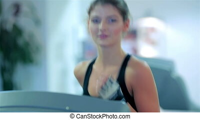 Young cute girl running in the gym smiling and looking at the camera