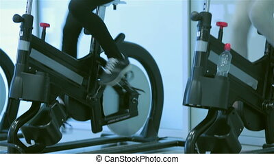 Two young ladies girl pedaling on the simulator and looking...