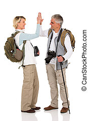 senior hiking couple giving high five - excited senior...