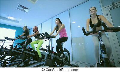 Fitness together on bicycles. Four friends pedal on a...