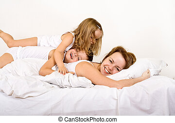 Happy morning - woman and kids on the bed