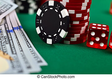 Poker chips, money and dice on a gaming table