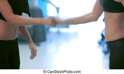 Close up girl shake hands while their friends do sports -...