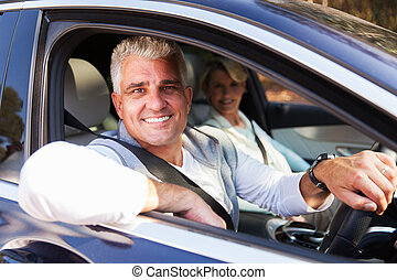 middle aged couple driving a car