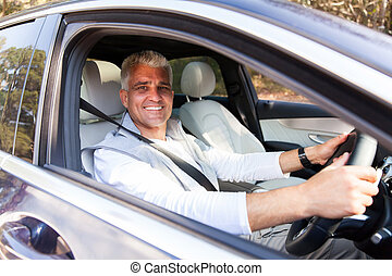 senior man driving his new car - handsome senior man driving...