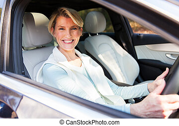 middle aged woman driving a car