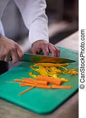 chef in hotel kitchen slice vegetables with knife and...