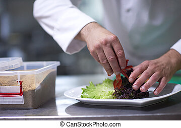 chef in hotel kitchen preparing and decorating food,...
