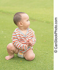 Asian baby boy playing sitting and crawling on the green grass field in the park