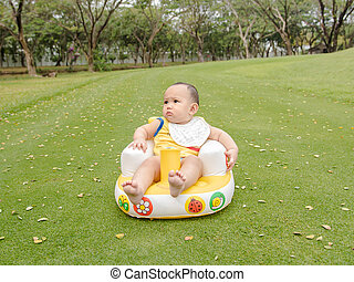 Adorable Asian baby boy crawling on the green grass field when he playing in the park.
