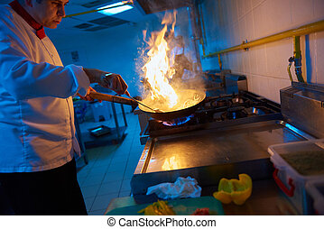 chef in hotel kitchen prepare food with fire - chef in hotel...