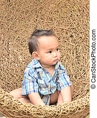 Boy in Rattan swing - Asian baby boy sitting in rattan swing