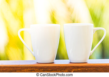 White coffee cup with outdoor view background - sunflare...