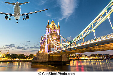 Airplane landing in London with Tower Bridge landmark.