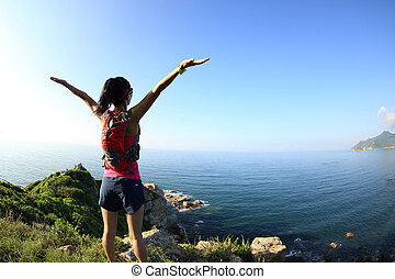 cheering young fitness woman open arms on seaside mountain...