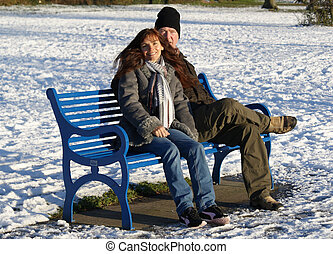 Quality time together - couple on a bench in a snow covered...