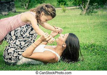 Mother and daughter playing on the grass at the day time.