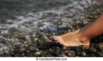 Women's legs on beach - Bare legs on pebble beach