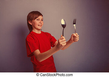 Teenager boy in red shirt twelve years holding spoon and...