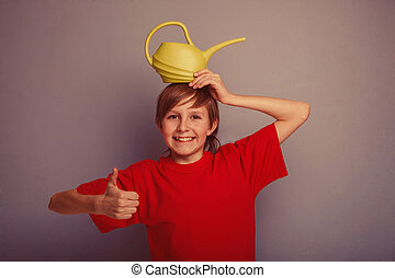 teenager boy twelve years in red shirt holding watering can...