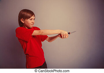 Teenager boy twelve years in the red t-shirt with knife evil...