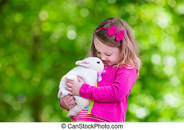 Little girl playing with rabbit - Children play with real...