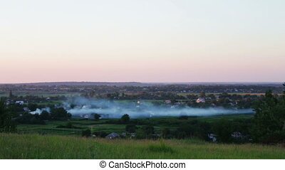 The landscape of the plain where the houses are fire and smoke haze.