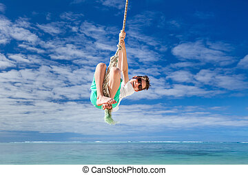 Cute boy swinging - Cute boy having fun swinging on a rope...