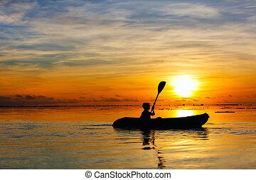 Boy kayaking at sunset
