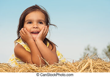 Little girl lying on a haystack Annapolis Valley, Nova...