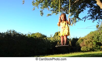 Little girl swinging. - Caucasian little girl playing swing...