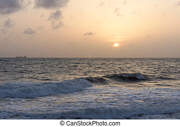 Sunset over sea with waves