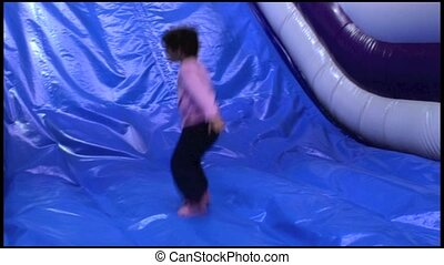 Child jumps on Inflatable slided - Little girl plays and...